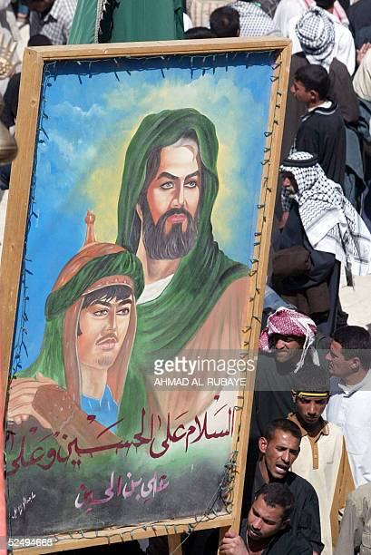 Shiite Muslim pilgrim hold up a large banner depicting the Imam Hussein and Imam Ali 30 March 2005 in the holy city of Karbala 100 kms south of...
