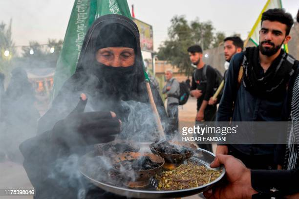 Shiite Muslim pilgrim is welcomed with burning incense as she takes part in a procession from the holy Iraqi city of Najaf towards the central shrine...
