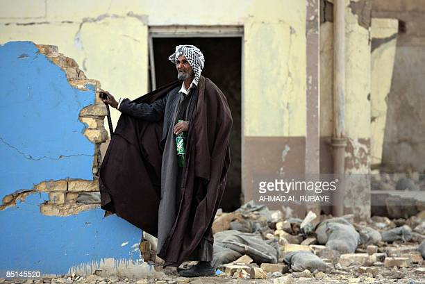 Shiite Muslim pilgrim man stands next to a destroyed building as he makes his way to the alAskareyya Shrine which embraces the tombs of the 10th and...
