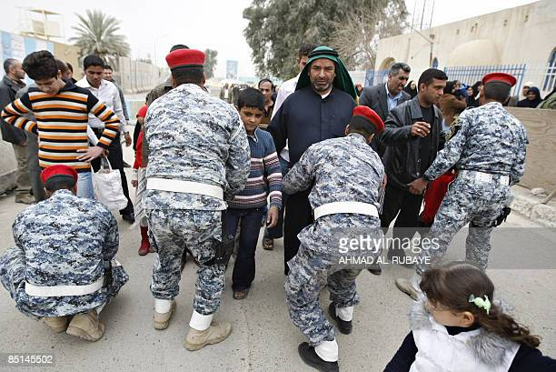 Shiite Muslim pilgrim men are frisked by security officers as they visit the alAskareyya Shrine which embraces the tombs of the 10th and 11th Imams...