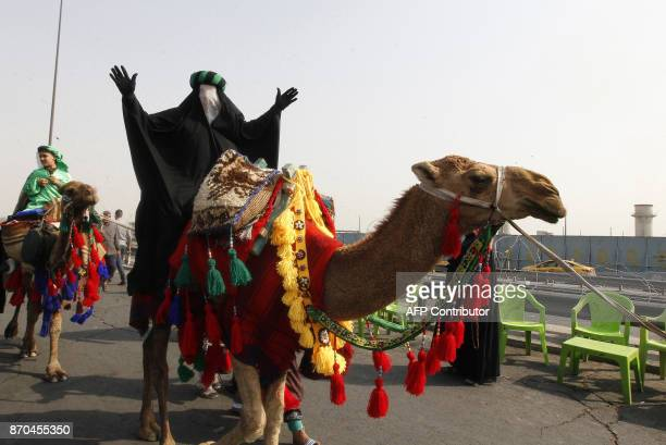 A Shiite Muslim pilgrim rides a camel on a road on the southern outskirts of Baghdad as they head towards the holy city of Karbala on November 5 2017...