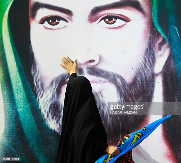 A Shiite Muslim pilgrim touchs a portrait of Imam Hussein in the Iraqi holy city of Najaf on November 26 2015 where they take part in the Arbaeen...
