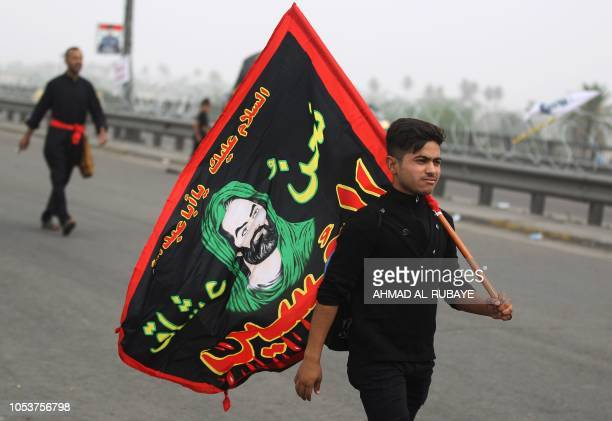 A Shiite Muslim pilgrim walks carrying a flag depicting the Prophet Mohammed's grandson Imam Hussein on the outskirts of the Iraqi capital Baghdad on...
