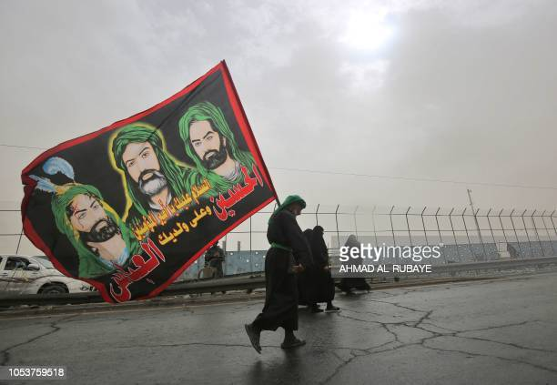Shiite Muslim pilgrim walks carrying a flag depicting the Prophet Mohammed's cousin Ali ibn Abi Taleb and his two sons Hussein and Abbas on the...