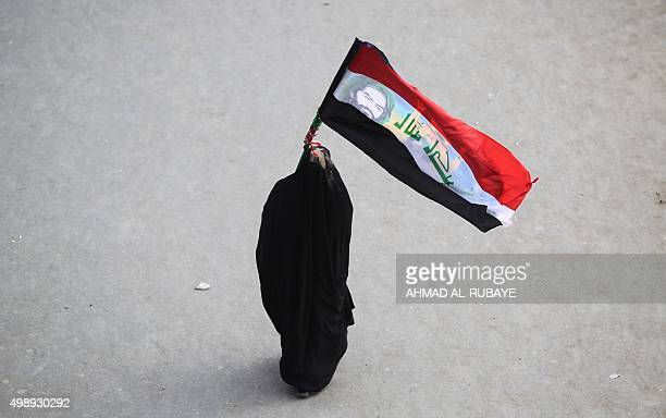 A Shiite Muslim pilgrim walks on a road in Baghdad's Dora district on November 27 on her way to the Iraqi holy city of Karbala to take part in the...