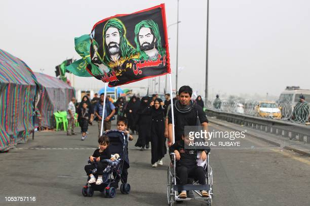 A Shiite Muslim pilgrim walks pushing a child stroller carrying a flag depicting the Prophet Mohammed's cousin Ali ibn Abi Taleb and his two sons...