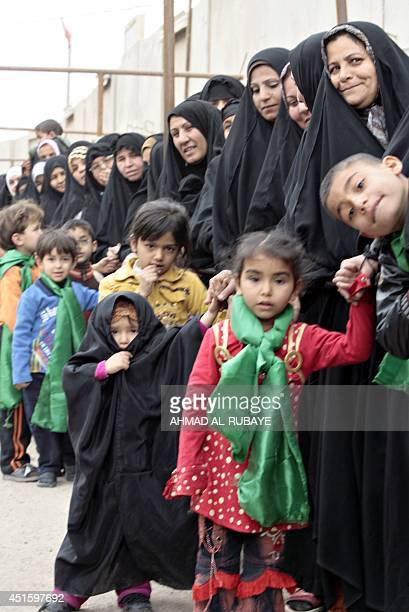 Shiite Muslim pilgrim women queue for a security search as they wait to visit the alAskari Shrine which embraces the tombs of the 10th and 11th Imams...