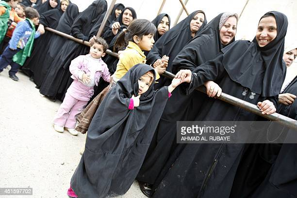 Shiite Muslim pilgrim women queue for a security search as they wait to visit the alAskarei Shrine which embraces the tombs of the 10th and 11th...