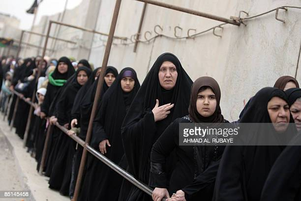 Shiite Muslim pilgrim women queue for a security search as they wait to visit the alAskareyya Shrine which embraces the tombs of the 10th and 11th...