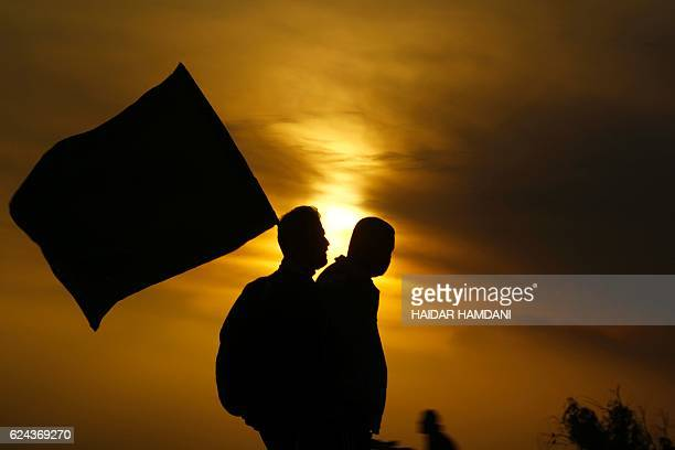 TOPSHOT Shiite Muslim pilgrims carry flags as they arrive at the entrance to the central Iraqi city of Karbala 120 kms south of the capital Baghdad...