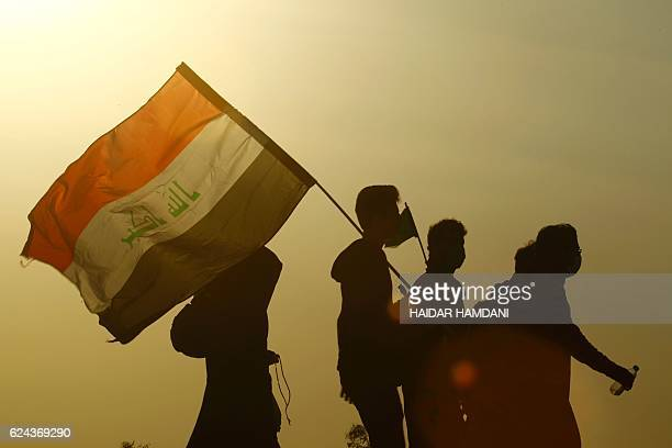 Shiite Muslim pilgrims carry flags as they arrive at the entrance to the central Iraqi city of Karbala 120 kms south of the capital Baghdad on...