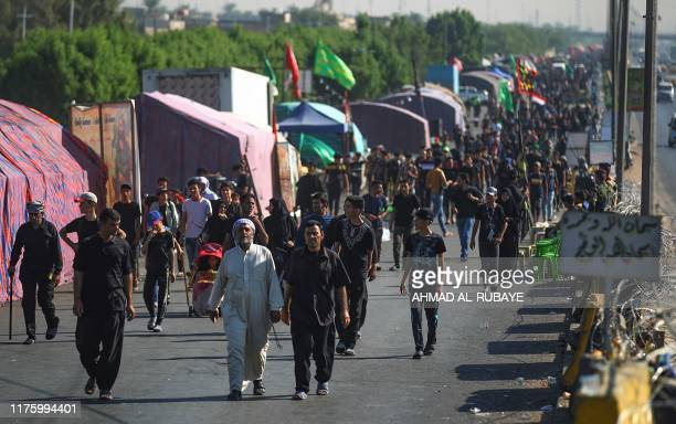 Shiite Muslim pilgrims take part in a procession from Baghdad to the shrine of Imam Hussein in Karbala on October 15 ahead of the Arbaeen religious...