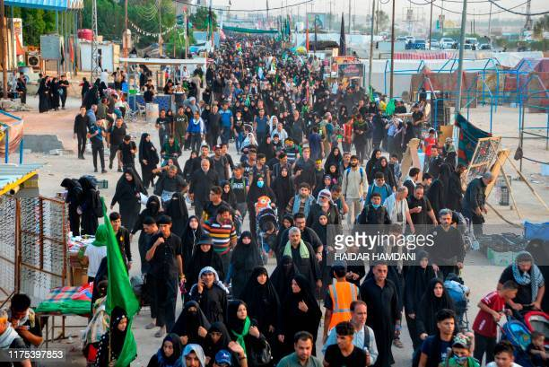 Shiite Muslim pilgrims take part in a procession from the holy Iraqi city of Najaf towards the central shrine city of Karbala on October 12 ahead of...