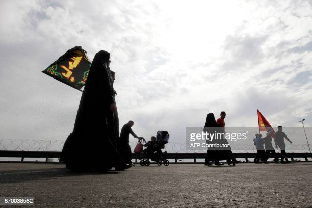 Shiite Muslim pilgrims walk on a road on the southern outskirts of Baghdad as they head towards the holy city of Karbala on November 4 2017 a week...