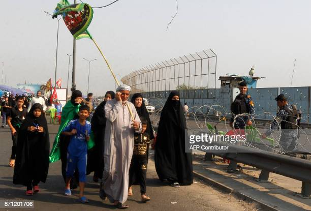 Shiite Muslim pilgrims walk past Iraqi security on a road on the southern outskirts of Baghdad as they head towards the holy city of Karbala on...