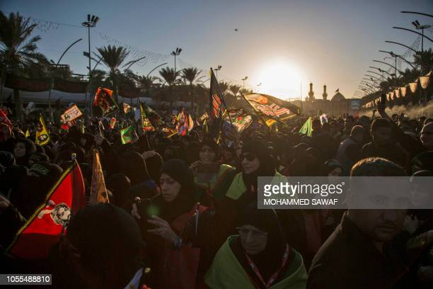 Shiite Muslim pilgrims wave religious flags as they gather near the shrine of Imam alAbbas in the central Iraqi holy city of Karbala on October 30...