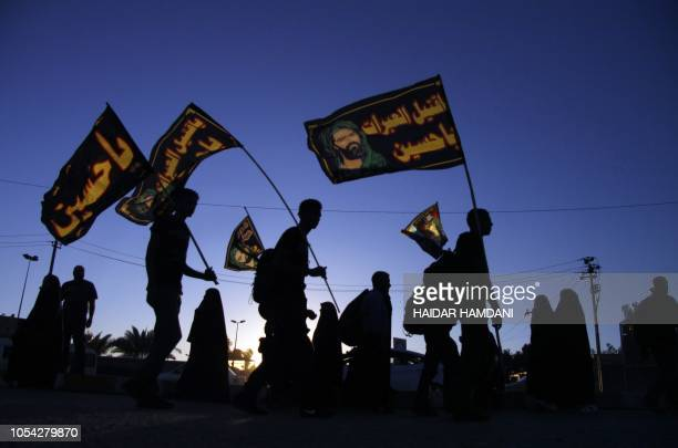 TOPSHOT Shiite Muslim pilgrims wave religious flags as they walk from holy city of Najaf towards the central Iraqi shrine city of Karbala on October...