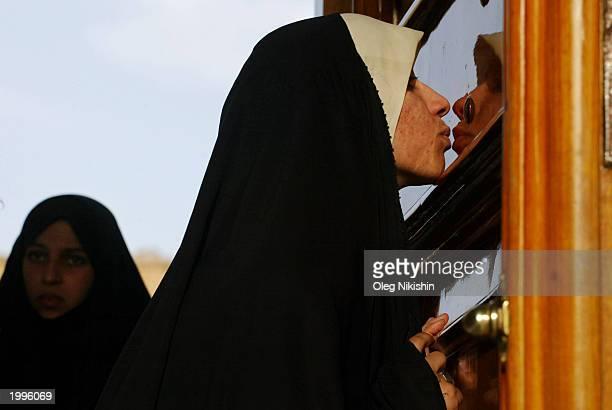 Shi'ite Muslim woman kisses the door at the entrance of the shrine of Imam Ali May 13, 2003 in Najaf, Iraq. Shi'ia leader Ayatollah Mohammed Baqir...