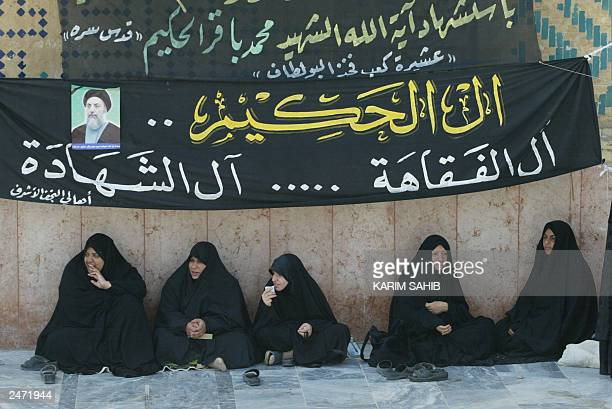 Shiite Muslim women sit under banners hailing Iraq's late Ayatollah Mohammed Baqer alHakim at the Imam Ali Shrine after the Friday noon prayer in...