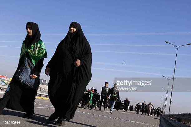 Shiite Muslim women walk on a main highway linking Baghdad to the central shrine city of Karbala, 120 kms south of the capital, on January 22, 2011...