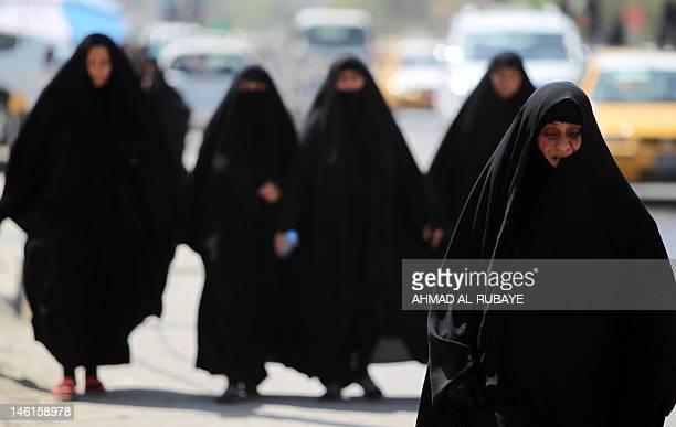 Shiite Muslim women walk to the Kadhimiyah area of north Baghdad, to mark the anniversary of the death of Imam Musa Kadhim on June 11, 2012. Four...