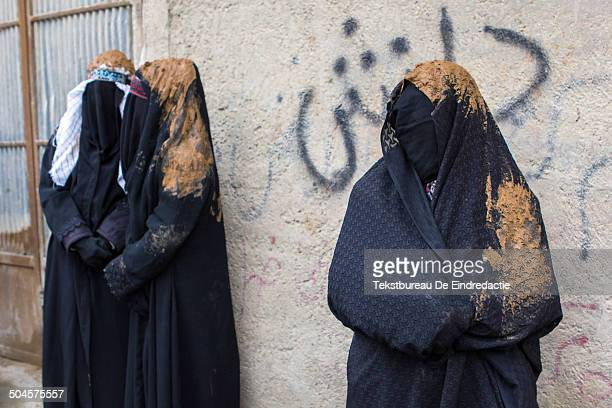 Shiite muslim women, wearing traditional black chadors and black veils, covered with fresh mud, standing before a wall with Persian graffiti, early...