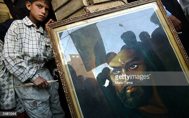 Shiite Muslims are reflected in a portrait of Imam Hussein the son of Imam Ali outside the shrine of Imam Ali to mark the anniversary of the death of...
