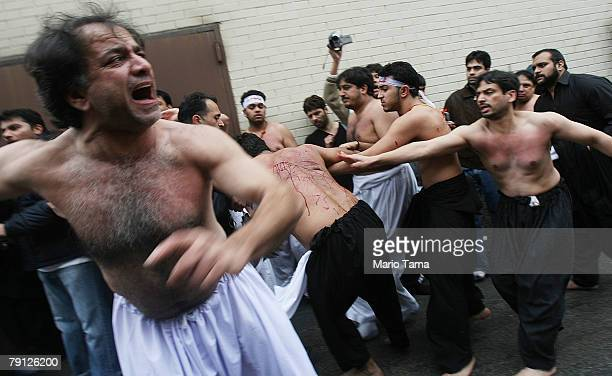 Shi'ite Muslims assist a worshiper who flagellated himself during a procession marking the festival of Ashura outside the alKhoei Islamic Center...
