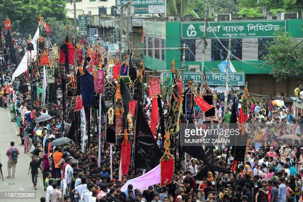 Shiite Muslims hold banners as they take part in a procession on the tenth day of Muharram which marks the day of Ashura, in Dhaka on September 10,...