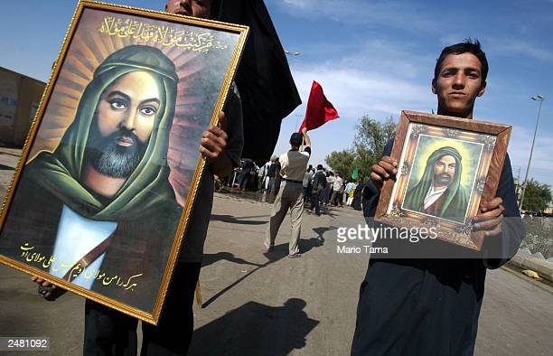 Shiite Muslims hold portraits of Imam Ali as they celebrate near the shrine of Imam Ali the soninlaw of Mohammed to mark the anniversary of the death...