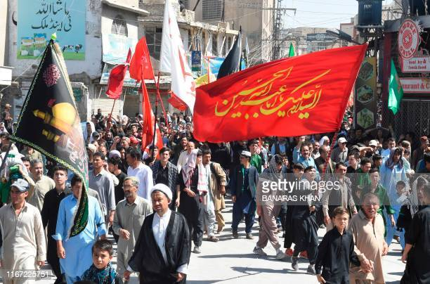 Shiite Muslims hold religious flags as they march during a procession on the tenth day of Muharram which marks the day of Ashura in Quetta on...