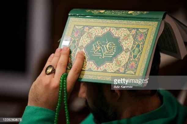 Shiite Muslims hold the Koran on their heads as they pray during the Lailat alQadr on May 16 2020 Baku Azerbaijan Access to all boulevards parks...