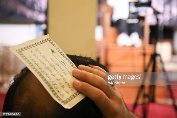 Shiite Muslims hold the Koran on their heads as they pray on Lailat alQadr on May 12 2020 Baku Azerbaijan Access to all boulevards parks mosques and...