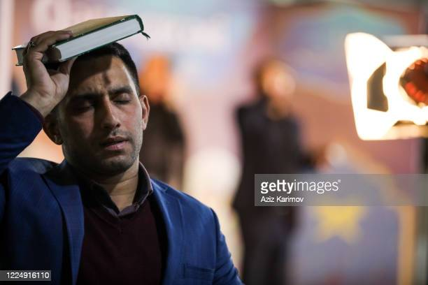 Shiite Muslims hold the Koran on their heads as they pray on Lailat alQadr at the FatimeyiZahra mosque on May 14 2020 Baku Azerbaijan Access to all...