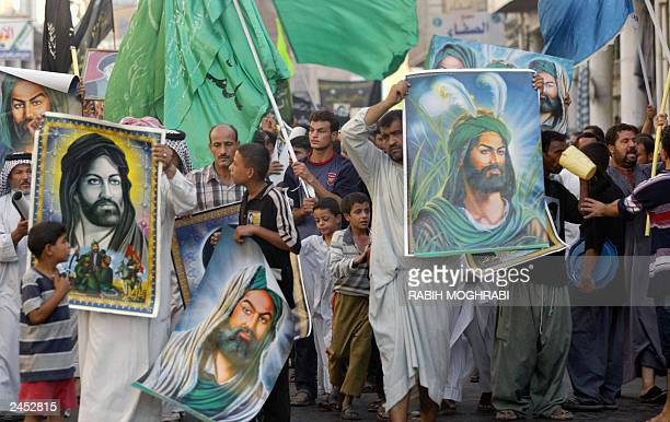 Shiite Muslims hold up pictures of Imam Ali cousin of Islam's Prophet Mohammed during the funeral ceremony of assassinated Ayatollah Mohammed Baqer...