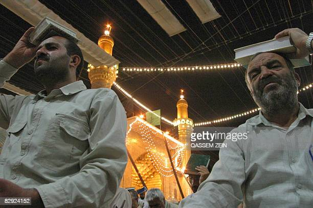 Shiite Muslims place the holy Koran on their heads as they recite prayers in the Imam Ali shrine in the southern city of Najaf some 160kms from...