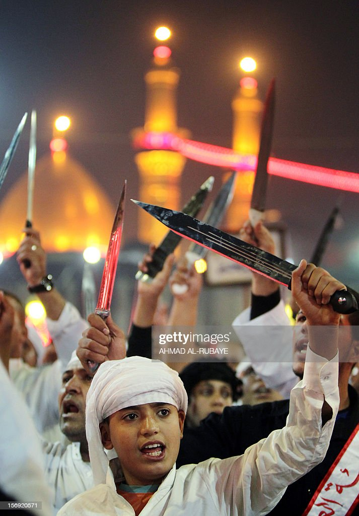 Shiite Muslims raise their swords outside the shrine of Imam Abbas early on November 25, 2012 in Karbala during the celebration of Ashura. Millions of pilgrims pour into the Iraqi shrine city of Karbala for the peak of commemorations for Ashura today, the most important day in the Shiite calendar, with security tight following mass-casualty attacks in previous years.
