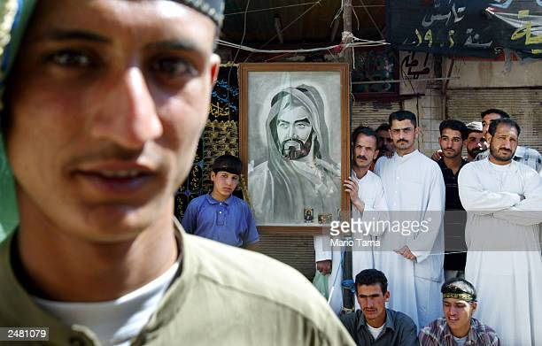 Shiite Muslims stand next to a portrait of Imam Hussein the son of Imam Ali outside the shrine of Imam Ali the soninlaw of Mohammed during...