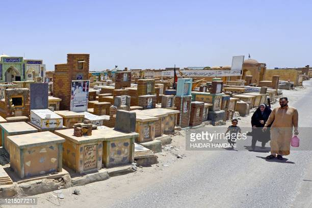 Shiite muslims visit the graves of their relatives at Wadi alsalam cemetery on the first day of the Eid alFitr holiday marking the end of the Muslim...