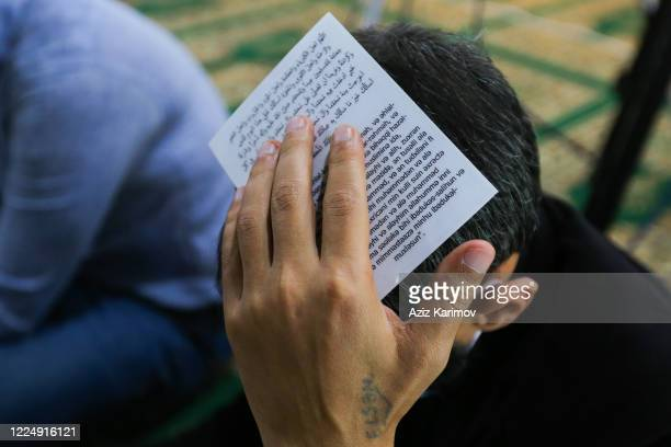 Shiite Muslims wear face masks and hold a piece of the Koran on their heads as they pray on Lailat alQadr at the FatimeyiZahra mosque on May 14 2020...