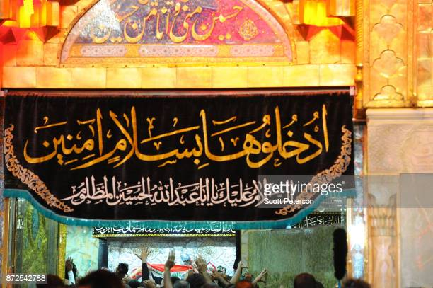 Shiite pilgrims raise their hands in reverence at the climax of days of marching by trying to touch the gilt tomb of Imam Hossein on arbaeen the...