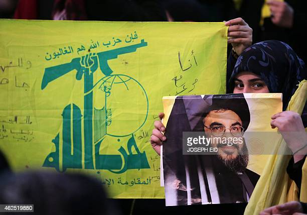 A Shiite supporter holds a poster showing Hassan Nasrallah the head of Lebanon's militant Shiite Muslim movement Hezbollah as he addresses supporters...