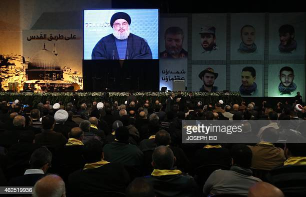 Shiite supporters watch Hassan Nasrallah the head of Lebanon's militant Shiite Muslim movement Hezbollah addressing them through a giant screen on...