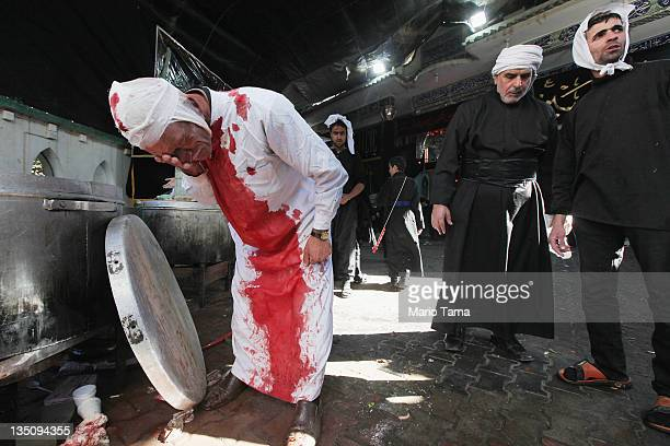 Shi'ite worshiper washes himself after cutting his scalp in a ritual display of mourning during an Ashura commemoration ceremony outside Kadhimiya...