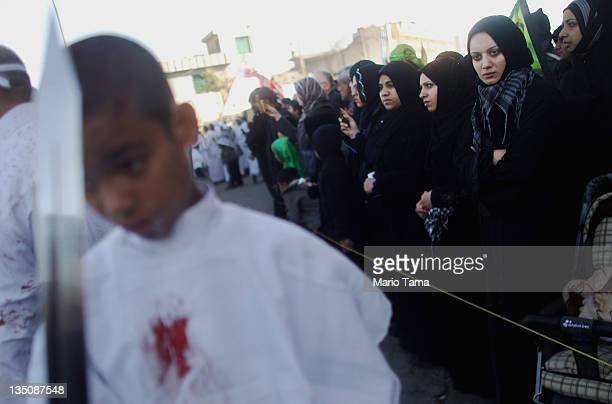 Shi'ite worshipers as others bleed after cutting their scalps in a ritual display of mourning during an Ashura commemoration ceremony outside...