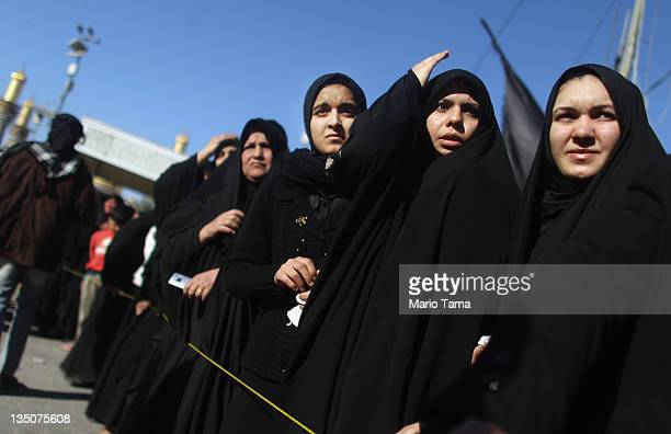 Shi'ite worshipers look on during an Ashura commemoration ceremony outside Kadhimiya shrine on December 6 2011 in Baghdad Iraq Ashura marks the death...