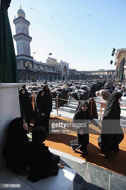 Shi'ite worshipers pray during an Ashura commemoration ceremony inside Kadhimiya shrine on December 6 2011 in Baghdad Iraq Ashura marks the death of...