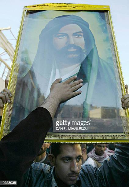 Shiite worshipper touches a portrait of Imam Ali for blessing as thousands of faithful headed to Imam Ali's shrine in the holy Iraqi city of Najaf...