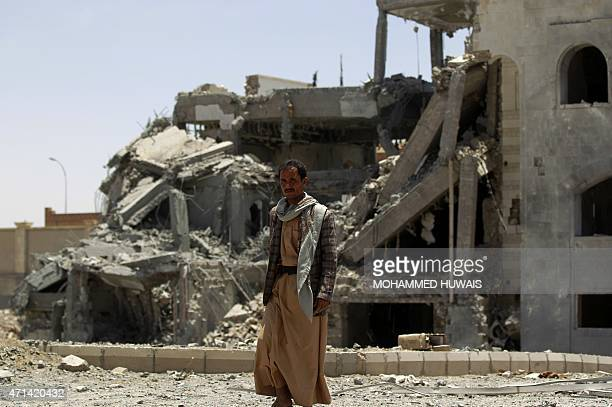 A ShiiteHuthi fighter walks in the yard of the residence of the military commander of the militant group Abdullah Yahya alHakim after an air strike...
