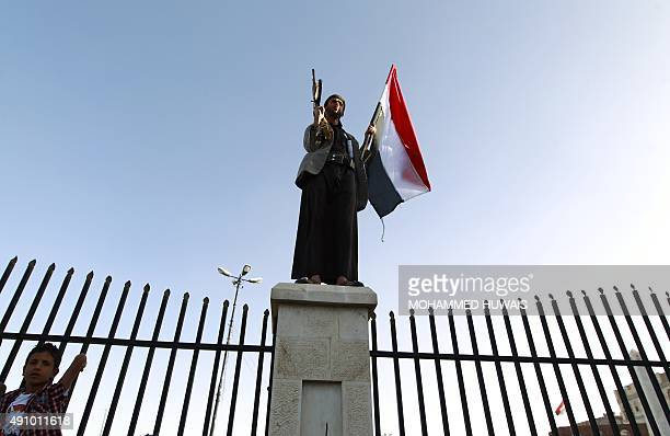 Shiite-Huthi supporter stands on a pillar holding a Yemeni flag during a protest in the capital, Sanaa, against ongoing military operations carried...